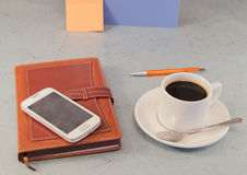 Brown organizer, white coffee Cup, mobile phone, grey background Royalty Free Stock Photography