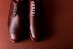 Brown oxford shoes on red background. Close up. Top view. stock photography