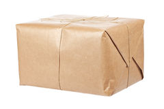 Brown package. A parcel wrapped in brown paper and tied with rough twine, isolated on white background. Shallow depth of field royalty free stock photo
