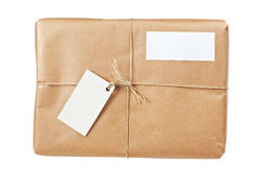 Brown package with blank labels. A parcel wrapped in brown paper and tied with rough twine and two blank labels, isolated on white background. Shallow depth of royalty free stock image