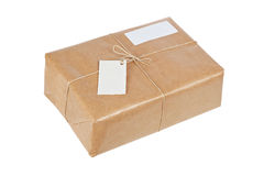 Brown package with blank labels. A parcel wrapped in brown paper and tied with rough twine and two blank labels, isolated on white background. Path included and stock images
