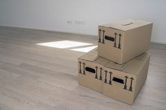 brown package card box in empty white room with windows and wooden flooring, windows and door in background - Moving Day royalty free stock image