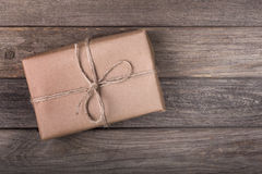 Brown Package on a Deck. Single brown package tied with string on a wood background Royalty Free Stock Photos