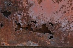 Brown paint on metal wall with corrosion. Royalty Free Stock Image