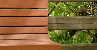 Brown painted bench next to a weathered wooden fence. In Juanita, Kirkland, Seattle royalty free stock photography