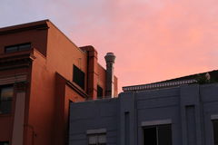 Brown Painted Building Near Orange Building during Sunset Royalty Free Stock Image