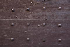 Brown painted wooden gate fixed with rivets. Background texture Royalty Free Stock Images