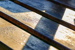 Brown painted wooden planks of bench in the rays of sun stock image