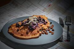 Brown Pancake With Brown Purple White Nut on Grey Round Plate Beside Silver Knife and Fork Royalty Free Stock Photos