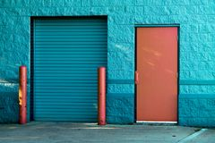 Brown Panel Door Near Roll-up Gate royalty free stock images