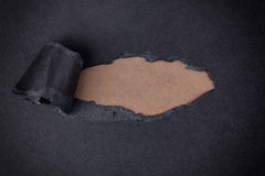 Brown paper background appearing behind torn black paper Royalty Free Stock Photo
