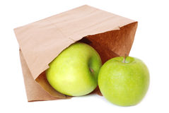 Brown paper bag with green apples Royalty Free Stock Images