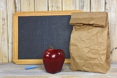 Brown paper bag with red apple and chalkboard Stock Image