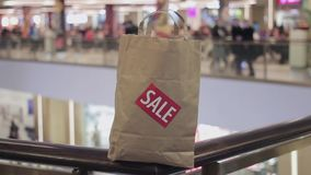 Brown paper bag with red sale sticker on it on handrail in shopping mall stock video