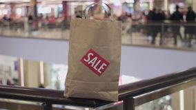Brown paper bag with red sale sticker on it on handrail in shopping mall stock video footage