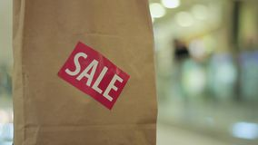 Brown paper bag with red sale sticker on it in shopping mall Close up stock video