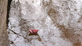 Brown paper boat of colored paper floats along the river bank. Brown paper boat of colored paper floats along river bank stock footage