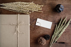 Brown paper box on old wood background with dried flower Royalty Free Stock Photography