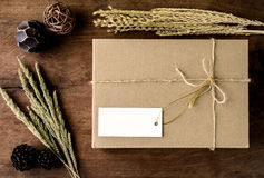 Brown paper box on old wood background with dried flower Royalty Free Stock Images