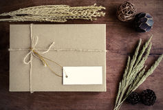Brown paper box on old wood background with dried flower Stock Photo