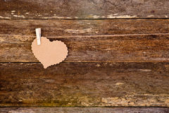 Brown paper - cardboard heart on clothespin on string on rustic Royalty Free Stock Image
