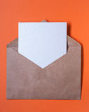 Brown paper envelop with blank letter inside on orange Royalty Free Stock Photography