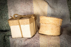 Brown paper gift box and round bamboo basket on fabric backgroun. D stock photography