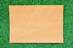 Brown paper on green grass Stock Photos