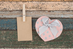 Brown paper hanging on the clothesline and Heart gift box on vintage wood Royalty Free Stock Images