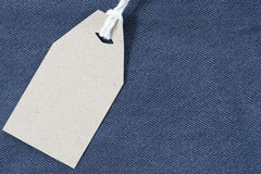 Brown paper label with hemp rope tied on denim or jeans. Stock Image