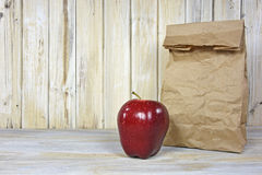 Brown paper lunch sack and apple Royalty Free Stock Photos