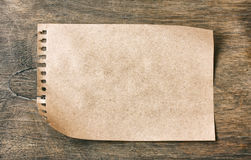 Brown paper notepad blank sheet on dark plywood Royalty Free Stock Photos