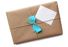 Brown Paper Package. Tied with string as a gift with a blank card for your text. on a white background with a clipping path royalty free stock photos