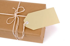 Brown paper package with white string and manila gift tag label isolated on white background, copy space Stock Photography