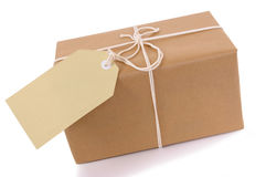 Brown paper package with white string, manila label or gift tag isolated on white background Royalty Free Stock Image