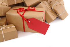 Isolated pile of brown packages, red gift label, copy space Stock Photography