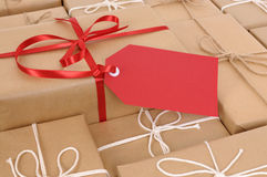 Red gift tag with several brown paper packages, copy space Stock Photography
