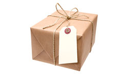 Brown paper parcel. With a blank luggage tag royalty free stock photography