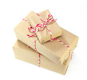 Brown paper parcel tied with red and white string on white backg Royalty Free Stock Photography
