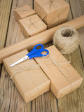 Brown paper parcels with paper string and scissors Royalty Free Stock Images