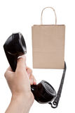 Brown paper shopping bag and telephone Royalty Free Stock Image