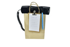 Brown paper shopping bag with telephone on white background Royalty Free Stock Images