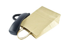 Brown paper shopping bag with telephone on white background royalty free stock photos