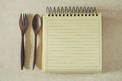 Brown paper spiral notebook and wood spoon and fork Royalty Free Stock Photos