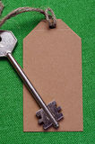 Brown paper tag attached to the metal silver key on the green  f Stock Photo