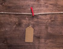 Brown paper tag hanging on a rope. Brown wooden background Royalty Free Stock Images