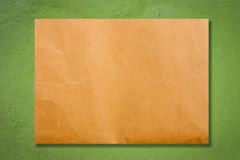 Brown paper on wall. Brown paper on green cement wall Royalty Free Stock Photography