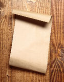 Brown paper on wood Royalty Free Stock Images