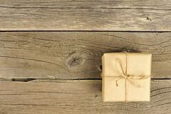 Brown paper wrapped gift box with bow on rustic wood Stock Images