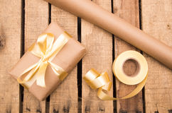 Brown paper wrapping present lying on wooden surface with golden ribbon around it, as seen from above Royalty Free Stock Photos